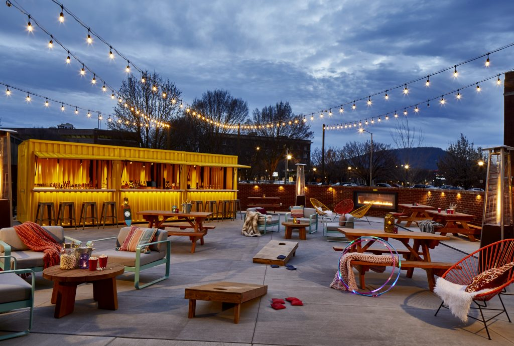 The Railyard, Moxy's outdoor patio space for activations and events. The bright yellow bar once served as a railcar, adding to the theme.